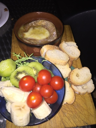 Queso de oveja fundido con tomates y fruta